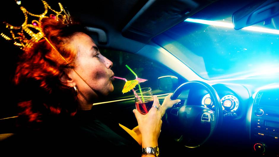 Eine Frau sitzt am Steuer eines Autos und trinkt Alkohol
