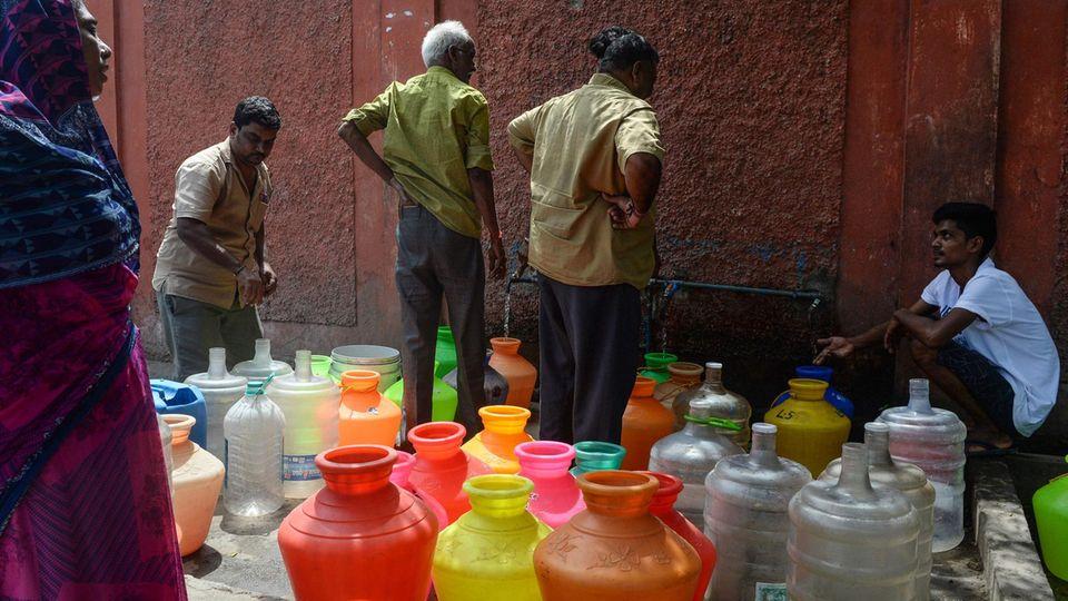 Indische Männer stehen an einer Ausgabestelle an, um Wasser in mitgebrachte Behälter abzufüllen.
