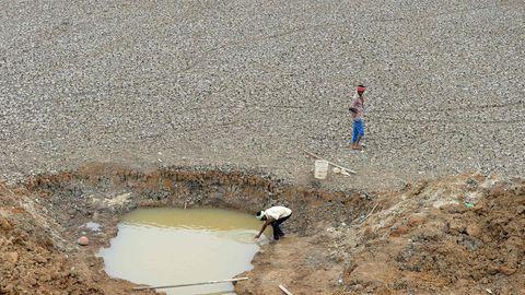 Zwei Männer stehen an einem Wasserloch, um Trinkwasser abzufüllen.