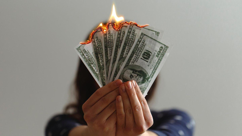 Frau mit brennenden Geldscheinen in der Hand