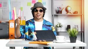 Mann am Schreibtisch mit Glas in der Hand