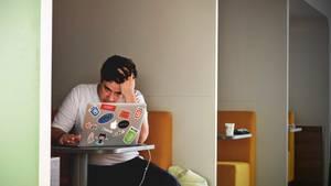 Junger Mann sitzt verzweifelt vor dem Computer.