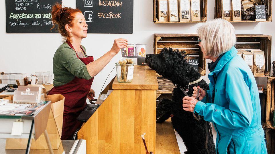 Verkäuferin reicht Hund einen Snack über Thresen