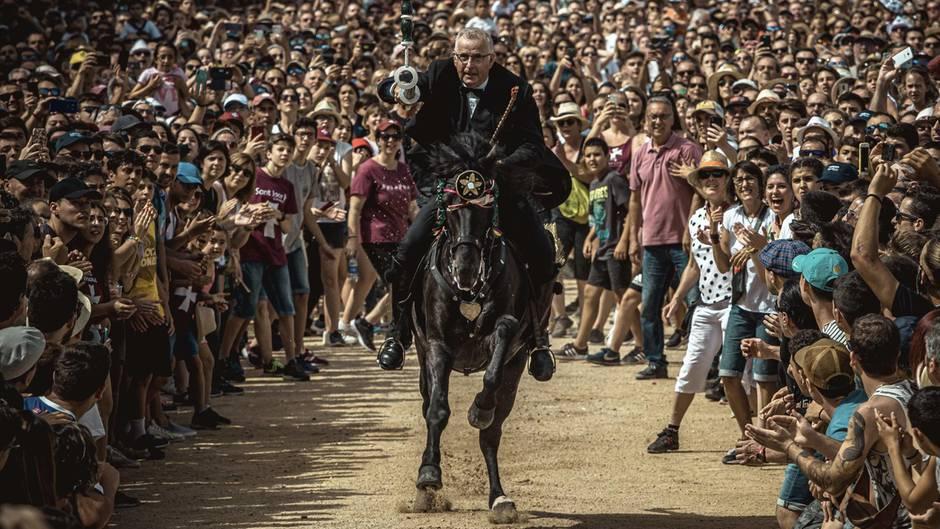 """Ciutadella De Menorca, Spanien.Ein Reiter richtet während des Trainings für das Mittelalterturnier """"Jocs des Pla""""seine Lanze auf einige Ringe, die aufgehängt sind. Die Spiele und Paraden, die während des Festivals von Sant Joan in Ciutadella, Menorca, stattfinden, ziehen Tausende von Menschen an."""