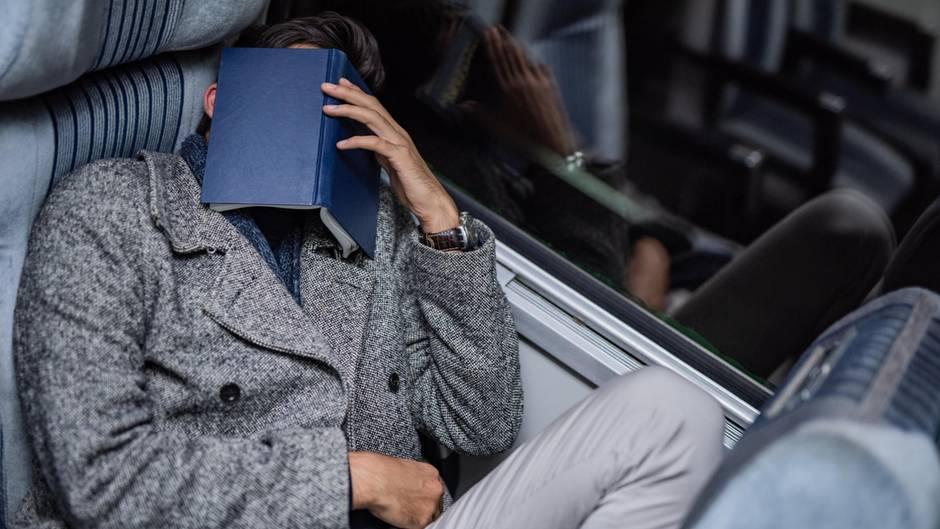 Mann mit Buch auf Gesicht schläft im Zug