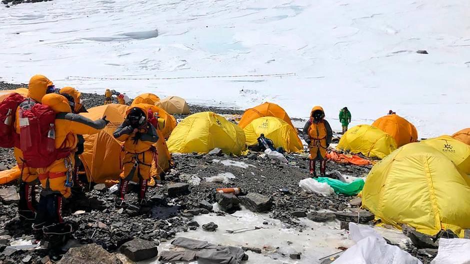 Bergsteiger in dicken Jacken stehen im Basiscamp am Mount Everest zwischen lauter verlassenen Zelten.Im Hintergrund liegt Schnee