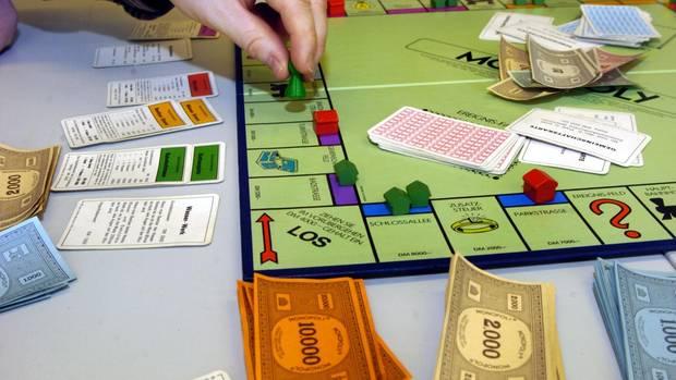 Ein Mensch spielt Monopoly