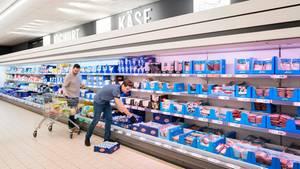 Mitarbeiter eines Supermarkts räumen Produkte ins Kühlregal