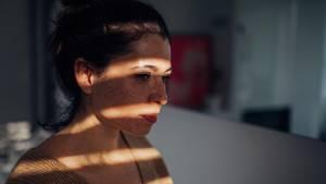 Warentest prüft Onlinetherapie bei Depression: Eine junge Frau sieht aus dem Fenster