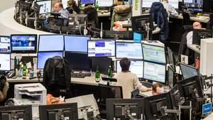 Menschen arbeiten an Arbeitsplätzen mit je 6 Bildschirmen.