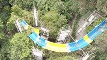 Zwischen Bäumen stehen Gerüste, die eine gelb-blaue Wasserrutsche halten