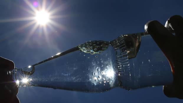 Hitzewelle – Frau trinkt bei Sonnenschein aus einer Wasserflasche