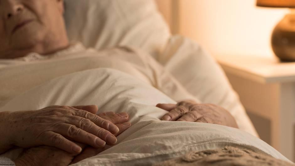 Ein gebrechlicher alter Mann liegt im Bett