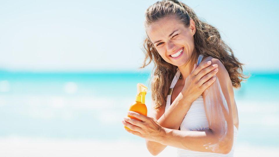 Stiftung Warentest prüft Sonnencreme 2019: Eine Frau steht am Strand und cremt sich mit Sonnencreme ein