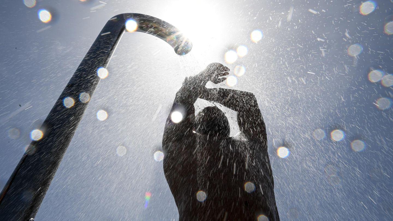Ein Badegast duscht sich im Strand- und Freibad nach dem Baden im Bodensee. Rund 20 Grad hat der Bodensee bei Friedrichshafen.