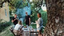 Freunde sitzen im Garten und grillen
