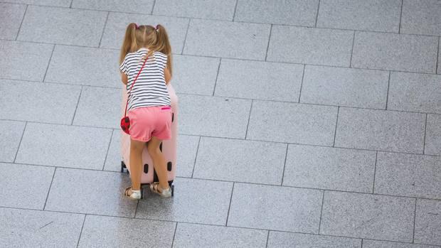 Ein kleines Mädchen schiebt einen Koffer durch einen Flughafen (Symbolbild)