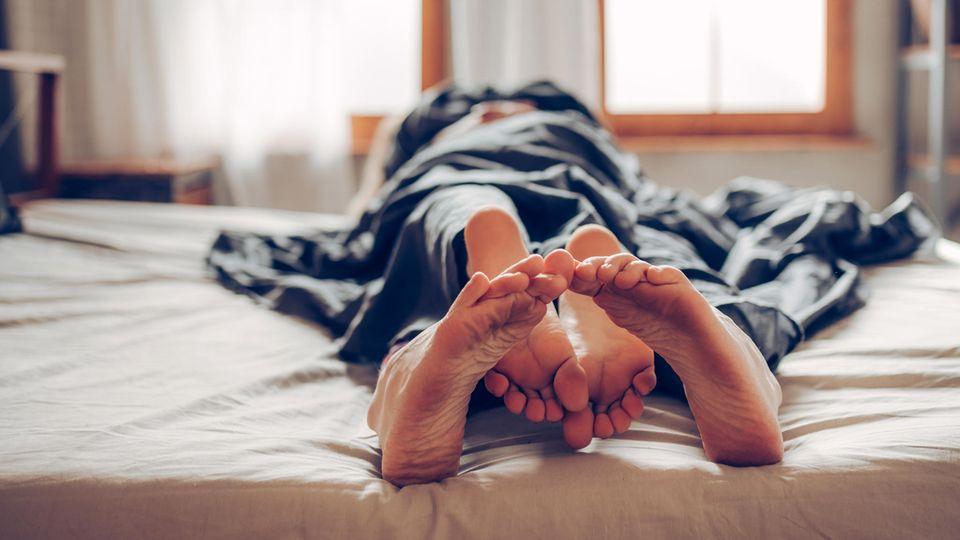 Zwei Menschen liegen im Bett