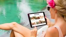 Eine Frau liest am Pool auf einem Tablet