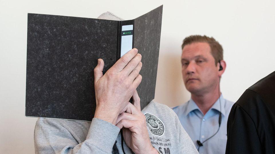 Hauptangeklagter im Fall Lügde mit Aktenordner vor dem Gesicht - im Hintergrund ein Wachmann