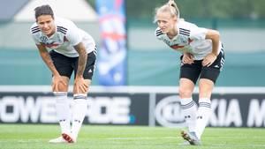Dzsenifer Marozsan (l.) und Lea Schüller machen Dehnübungen. Am Samstag geht es im Viertelfinale gegen Schweden.