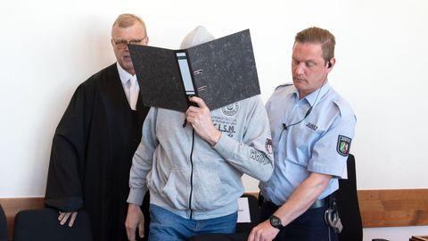 Der Angeklagte Andreas V. betritt mit einem Aktenordner vor dem Gesicht den Gerichtssaal
