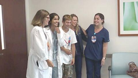 Eine Gruppe junger Menschen steht lachend in einem Krankenhaus, als wollten sie ein Gruppenfoto machen.