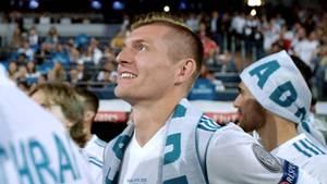 Toni Kross, ein junger Mann mit kurzen, blonden Haaren, steht im weißen Trikot auf dem Platz und lächelt
