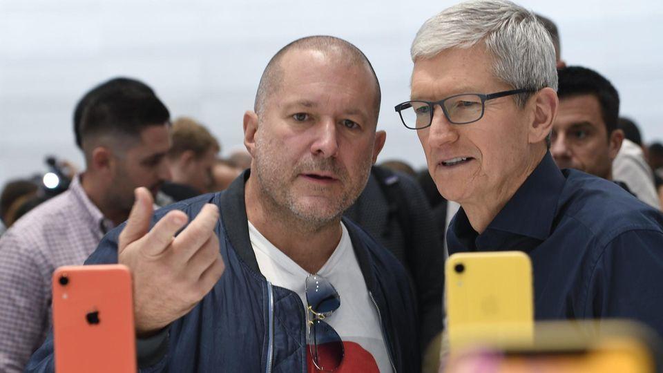 Designchef von Apple John Ive schaut sich mit einem zweiten Mann iPhones an.