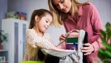 Mutter und Tochter räumen eien Rucksack auf