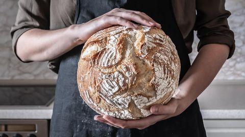 Ein Mensch hält ein rundes Brot in der Hand.