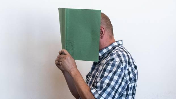 Heiko V. verdeckt sein Gesicht mit einer Aktenmappe.