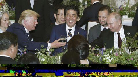 Leicht verdeckt sieht man hier US-Präsident Donald Trump und seinen russischen Amtskollegen Wladmir Putin anstoßen