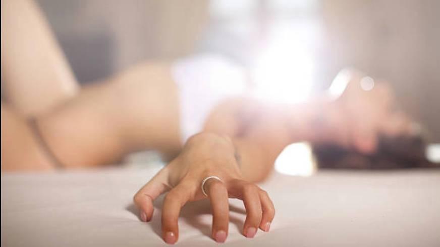Die Hand einer Frau mit Ehering. Im Hintergrund sieht man die Frau, wie sie leicht bekleidet auf einem Bett liegt.