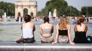 Vier Frauen sitzen bei heißen Temperaturen am Louvre auf dem Beckenrand eines Springbrunnens