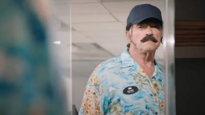Arnold Schwarzenegger im bunten Hemd mit Schnurrbart und Cap.