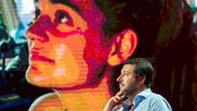 """Matteo Salvini, Innenminister von Italien, spricht während einer TV-Sendung. Auf der Monitorwand im Hintergrund ist die Kapitänin des Rettungsschiffs """"Sea Watch 3"""" eingeblendet."""