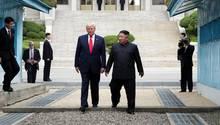 Kim Jong-Un und Donald Trump gehen gemeinsam über die Grenze zwischen Nord- und Südkorea.