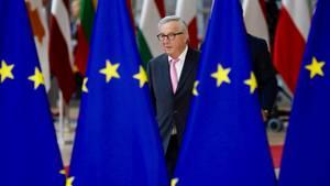 Ein Mann mit grauem Seitenscheitel und Brille läuft im Anzug zwischen Europa-Flaggen hindurch
