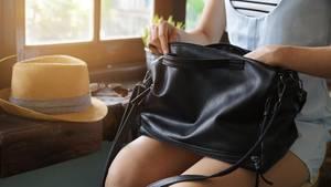 Eine Frau öffnet ihre Handtasche, die auf ihrem Schoß liegt