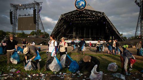 Mit Müllbeuteln ausgestattet, räumen Helfer das Festivalgelände auf