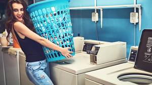 Shot of an attractive young woman holding a basket of washing while standing inside of a laundry room during the day