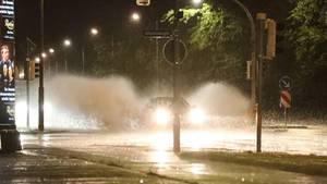 Ein Auto am Petriförder spritzt das Regenwasser durch die Luft - Unwetter mit Starkregen und Gewitter.