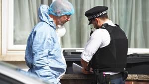Ein Forensiker spricht mit einem Polizisten am Tatort