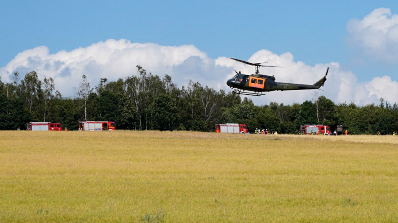 Ein Hubschrauber der Bundeswehr landet auf einer Wiese in der Nähe der Absturzstelle