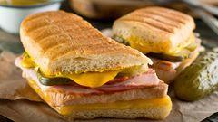 Cuban Sandwich  Das vor allem im Süden der USA beliebten Sandwiches wird auch Cubano genannt. Und es kommt nicht wie der Name vermuten mag aus Cuba. Aber Kubaner haben ein ähnliches Sandwich mit Fisch und Cassava-Brot gemacht, die Spanier aber brachten den Käse, das Weißbrot und das Schweinefleisch. Anfang der 1800er Jahre florierte der Tabakimport zwischen Kuba und Süd-Florida. Die Arbeiter brauchten einen schnellen Snack, so wurde das Sandwich geboren. Heute kennt man das Cubano mit gebratenem Schweinefleisch, Schinken, Schweizer Käse und Essiggurke.