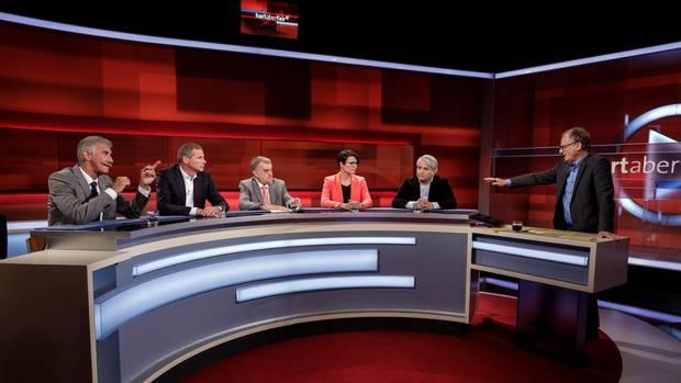 In einem Fernsehstudio mit rötlichem Hintergrung sitzen an einem halbrunden Tisch vier Männer und eine Frau. Rechts steht einer