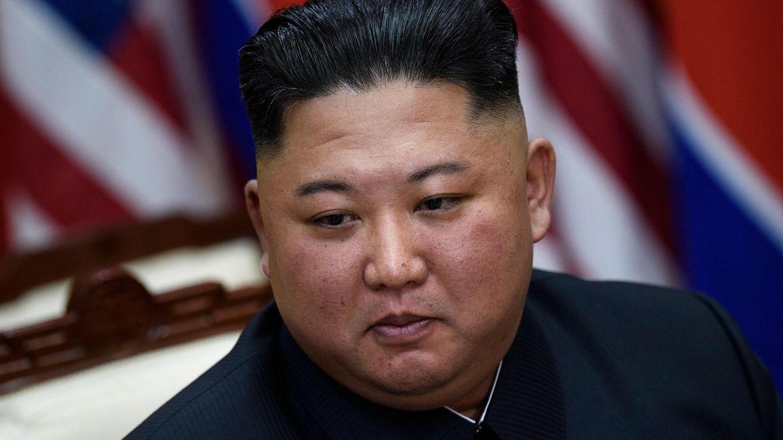 Kim Jong Un, ein wohlgenährter Mann mit schwarzem Bürstenschnitt, sitzt vor einer nordkoreanischen und einer US-Flagge