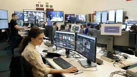 Eine Frau mit langen, braunen Haaren sitzt vor zwei Monitoren und bedient mit rechts eine Maus