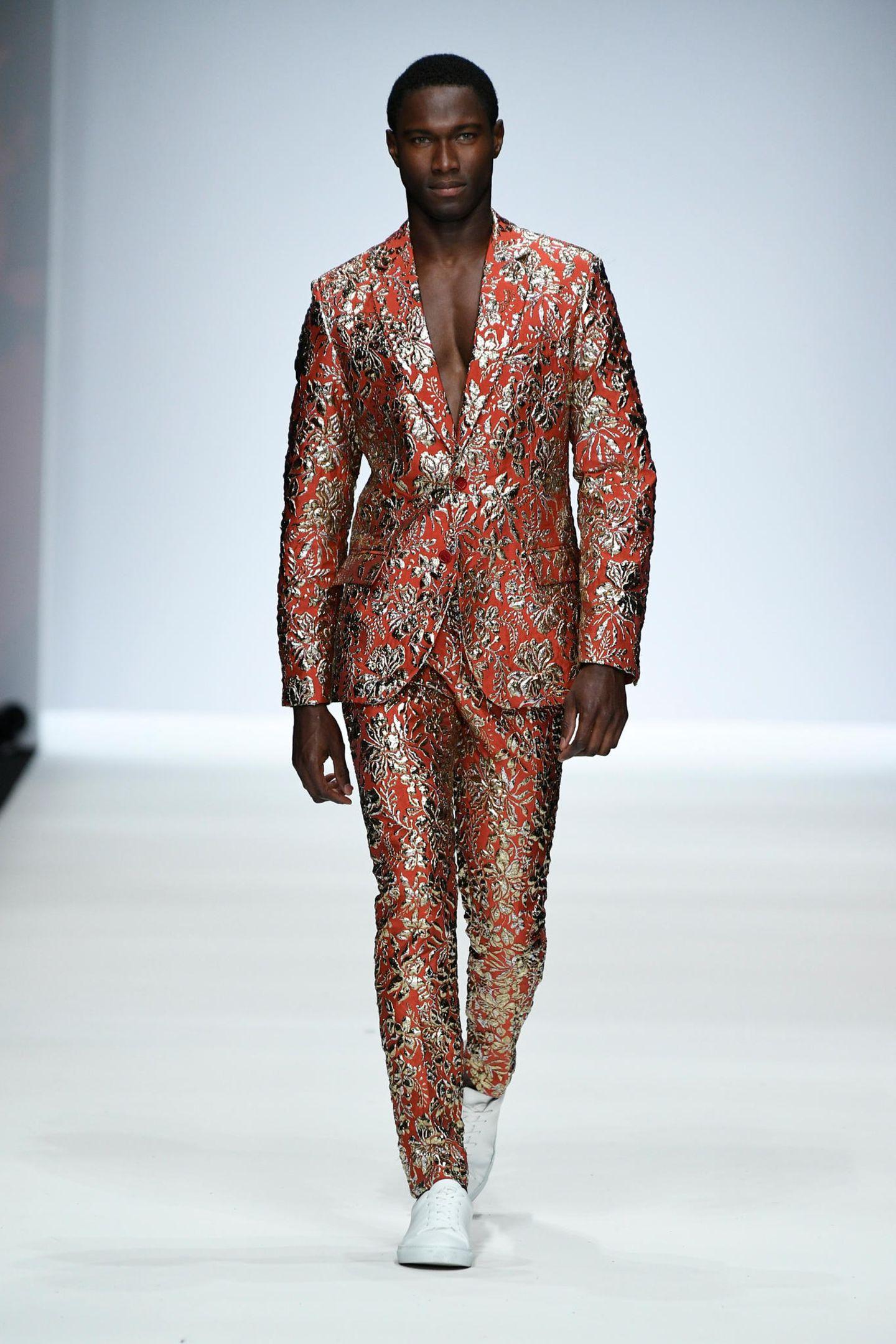 """In seiner Show auf der Berliner Fashion Week geht Guido Maria Kretschmer auf eine modische Reise mit dem Orientexpress - daher darf es auch bei den Männern ausgefallener sein,wie hier in einem rostfarbenen Glitzer-Anzug. Wenn es nach dem Designer geht, hört die Extravaganz dort noch lange nicht auf: """"Der Ohrring ist wieder zurück."""" Der wurde schließlich auch in den 80ern von vielen Männern getragen, aber Achtung: """"Das ist typabhängig."""" Riesige Tunnel seien aber in jedem Fall ein absolutes No-Go, sagte Kretschmer der DPA."""